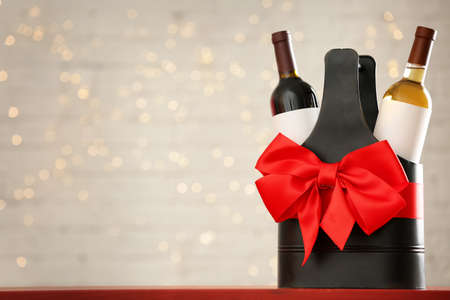 Bottles of wine in holder with bow against blurred lights. Space for text