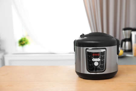 New modern multi cooker on table indoors. Space for text