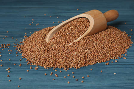 Wooden scoop with uncooked buckwheat on table Banco de Imagens