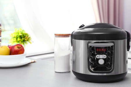 New modern multi cooker and jar of flour on table in kitchen. Space for text