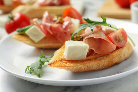 Plate of tasty bruschettas with prosciutto on table, closeup
