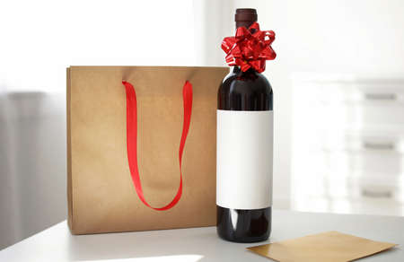 Bottle of wine, card and paper bag on table in light room