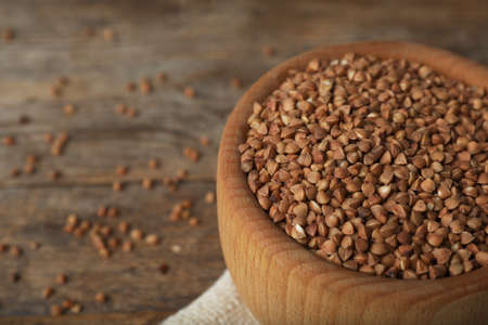 Uncooked buckwheat in bowl on wooden table, closeup. Space for text