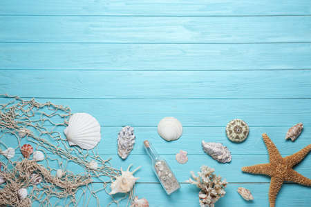 Flat lay composition with seashells and space for text on wooden background