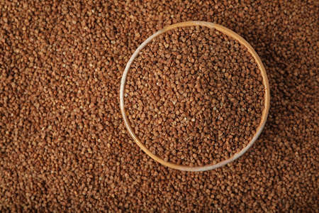Uncooked buckwheat in bowl on grains, top view. Space for text