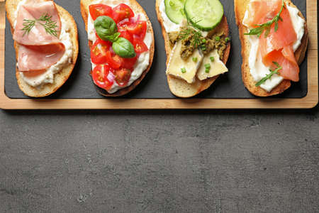 Board with different tasty bruschettas on grey table, flat lay. Space for text