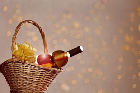 Bottles of wine in wicker basket with bow against blurred lights. Space for text