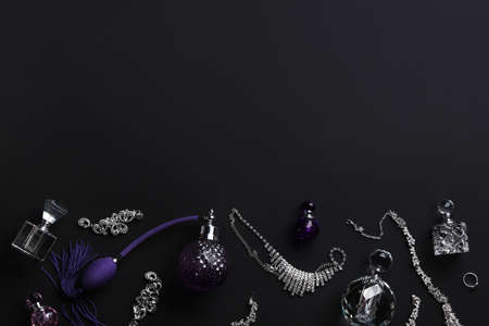 Composition with perfume bottles and jewellery on black background, flat lay. Space for text