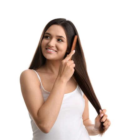 Hermosa mujer joven con peine sobre fondo blanco.