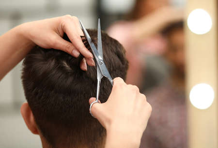 Barber making stylish haircut with professional scissors in beauty salon, closeup Stock Photo