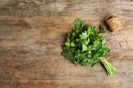 Bunch of fresh green parsley and twine on wooden background, flat lay. Space for text