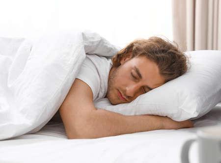 Hübscher junger Mann, der zu Hause auf Kissen schläft. Bettzeit