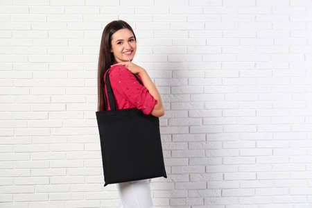 Beautiful young woman with stylish blank eco bag near brick wall, space for text