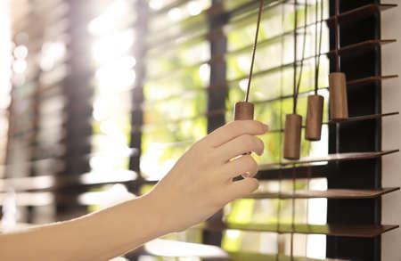 Mujer abriendo persianas horizontales en casa, primer plano