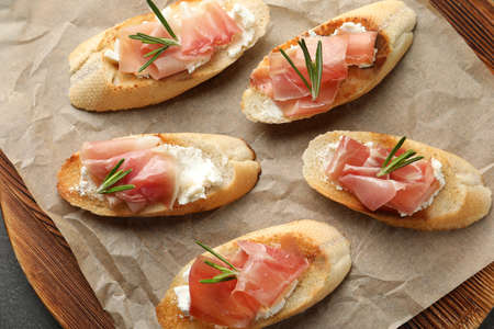 Tasty bruschettas with prosciutto and cream cheese on wooden board, top view