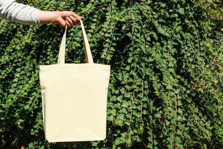 Woman holding eco bag outdoors, closeup. Mockup for design