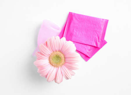 Menstrual pads and gerbera flower on white background, top view. Gynecological care Stock Photo