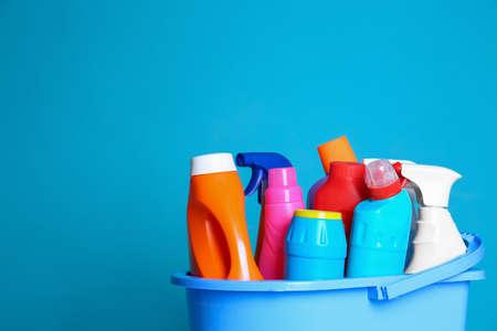Plastikeimer mit verschiedenen Reinigungsprodukten vor Farbhintergrund. Platz für Text
