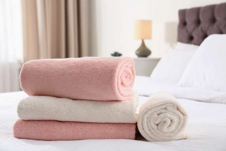 Folded and rolled soft towels on bed in room. Space for text
