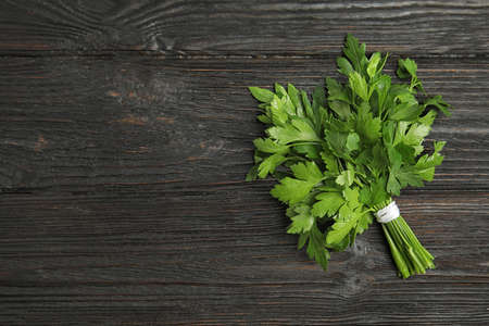 Bunch of fresh green parsley on wooden background, view from above. Space for text