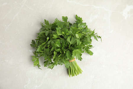 Bunch of fresh green parsley on light background, view from above