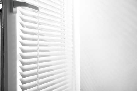 Window with closed horizontal blinds indoors. Space for text