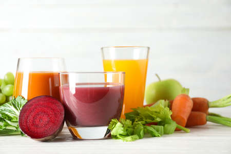 Glasses with different juices and fresh ingredients on table