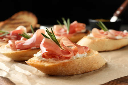 Tasty bruschettas with prosciutto and cream cheese served on table against dark background, closeup. Space for text