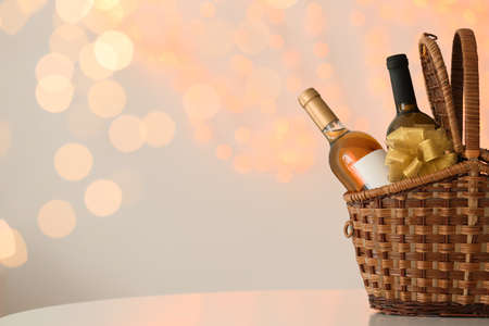 Wicker basket with bottles of wine against blurred lights. Space for text