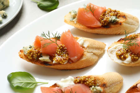Tasty bruschettas with salmon and blue cheese on plate, closeup