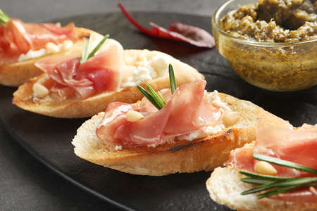 Tasty bruschettas with prosciutto and cream cheese served on table, closeup