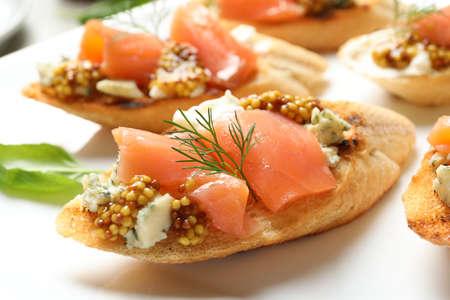 Tasty bruschettas with salmon and blue cheese on plate, closeup Reklamní fotografie