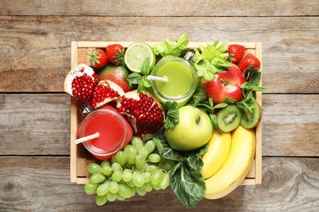 Wooden crate with juices in mason jars and fresh fruits on wooden background. Top view