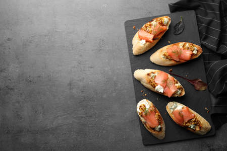 Slate plate with tasty bruschettas on grey table. Space for text
