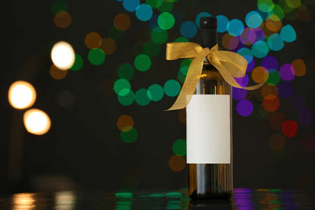 Bottle of wine with bow-knot on table against blurred lights, space for text. Bokeh effect