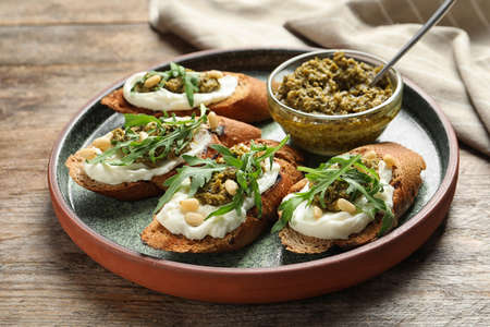 Plate with tasty bruschettas and pesto sauce on wooden table