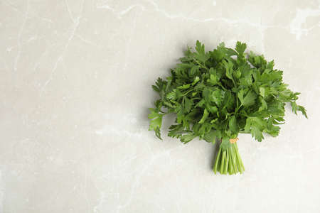 Bunch of fresh green parsley on light background, view from above. Space for text