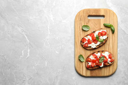 Board with tasty bruschettas on grey table, top view. Space for text