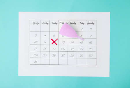 Calendar and menstrual cup on color background, top view. Gynecological care