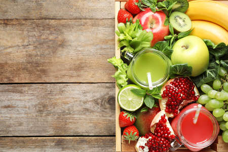 Wooden crate with juices in mason jars and fresh fruits on wooden background, top view. Space for text Stock Photo