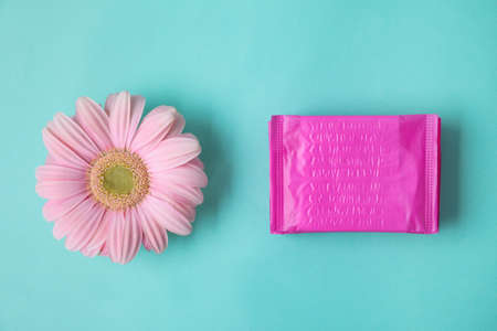 Flat lay composition with menstrual pads and gerbera flower on color background. Gynecological care Stock Photo