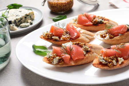 Tasty bruschettas with salmon and blue cheese served on table