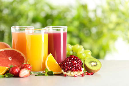 Three glasses with different juices and fresh fruits on table against blurred background. Space for text
