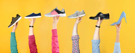 Set of people holding different stylish shoes on color background, closeup