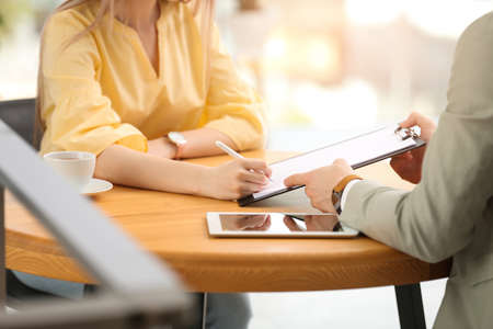 Woman signing contract with insurance agent in office, closeup
