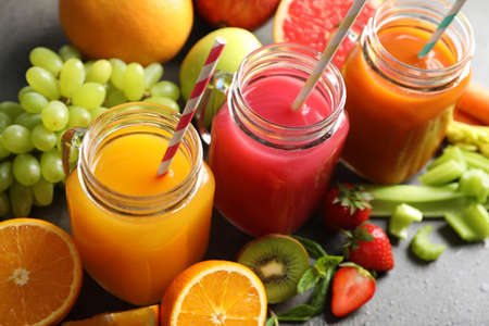 Different juices in mason jars and fresh ingredients on grey table