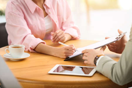 Woman signing contract with insurance agent in office, closeup Zdjęcie Seryjne - 125165334