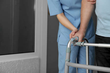 Nurse assisting senior patient with walker in hospital, closeup Stock Photo