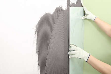 Arbeiter installieren Keramikfliesen an der Wand, Nahaufnahme. Platz für Text