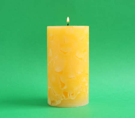 Alight scented wax candle on color background
